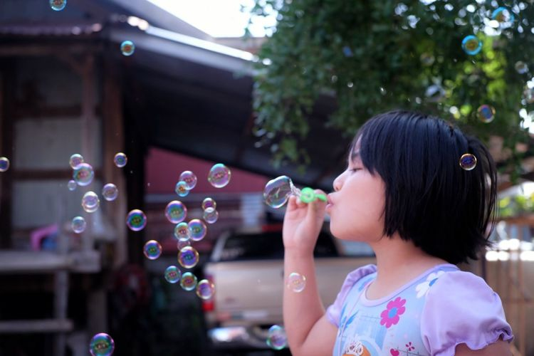 Girl blowing bubbles against trees