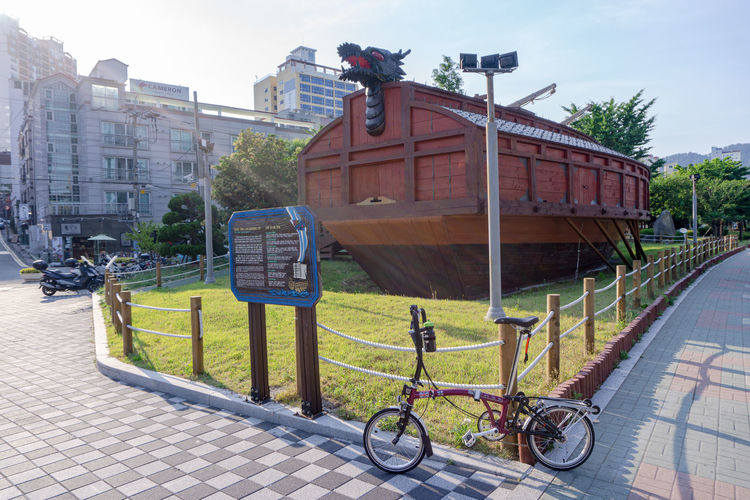 Bicycle by street against buildings in city