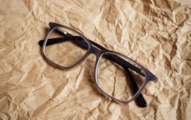Close-up of eyeglasses on crumpled brown paper