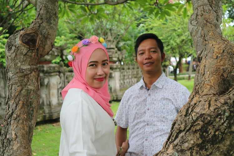 Portrait of a smiling young couple on tree trunk