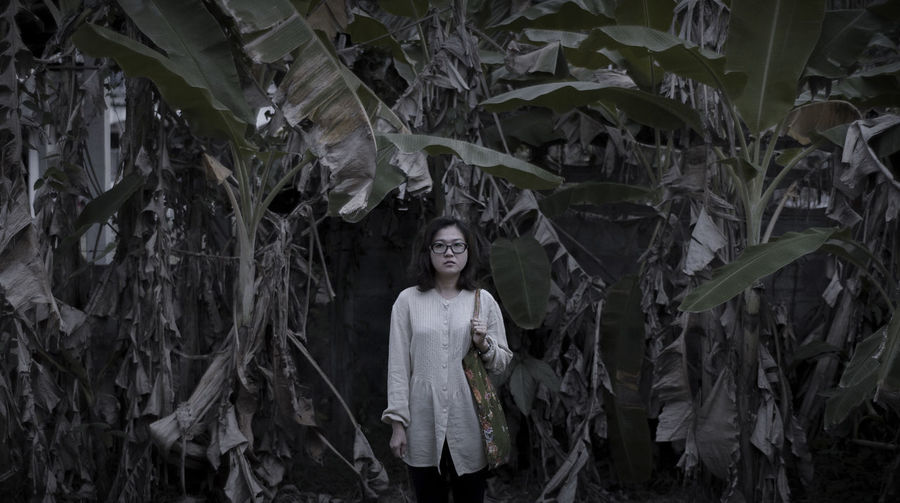 Portrait of woman standing amidst banana trees