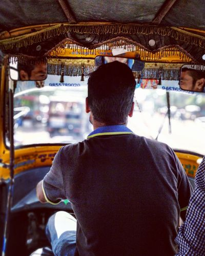 Rear view of man driving rickshaw