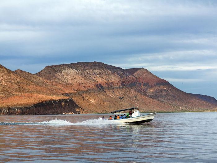 Boat sailing in sea by mountain at isla espiritu santo