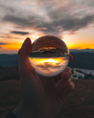 Cropped image of person holding crystal ball against sky during sunset