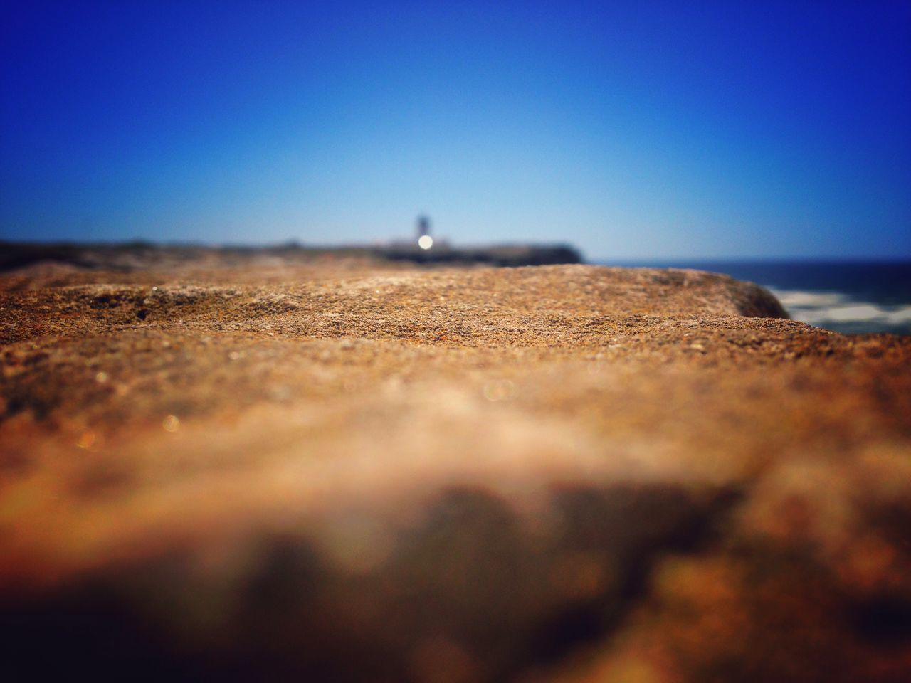 selective focus, clear sky, surface level, beauty in nature, nature, blue, tranquility, scenics, tranquil scene, outdoors, sky, no people, landscape, sea, tilt-shift, day