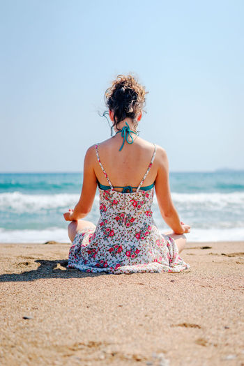 Rear view of woman meditating while sitting at beach against clear sky