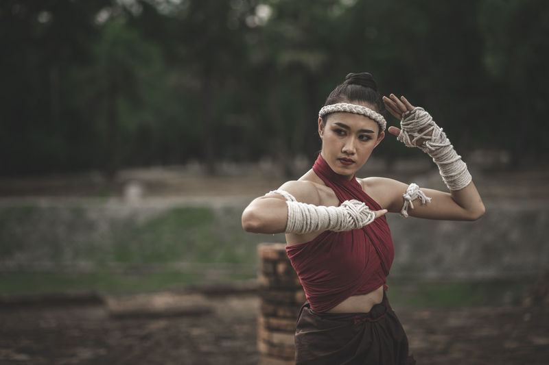 Thoughtful young woman practicing martial arts against trees