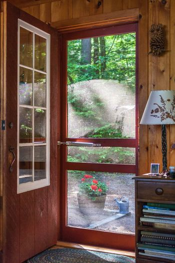 Home Is Where The Art Is Woodsy Cabin In The Woods Cabin Red Cabin Quaint House Quaint  Wooden Walls Family Home Homestead New Hampshire Lake Winnipesaukee Lake Cottage Cottage Watering Can Open Door Rustic Looking Outside Wood Floor Aged Memories The Secret Spaces