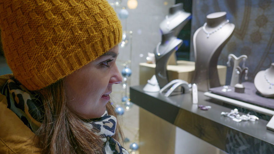 Close-up side view of young woman wearing warm clothing while shopping in jewelry store