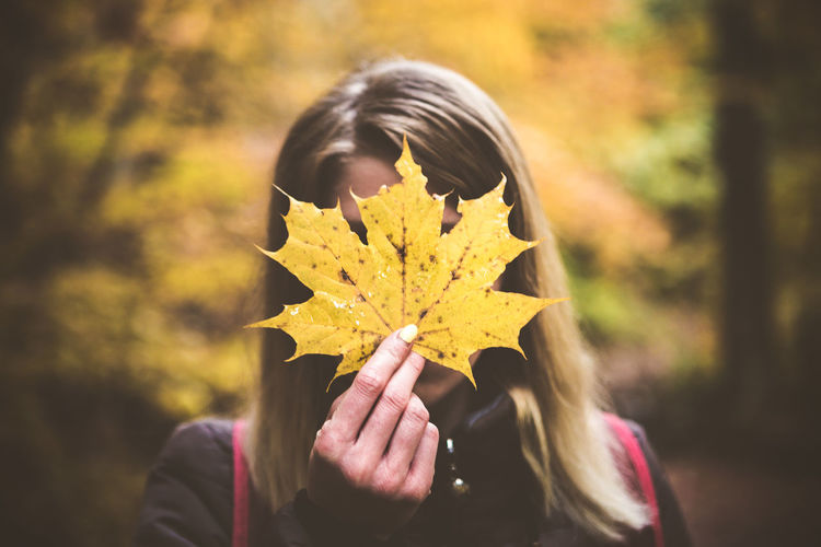 Woman Holding Maple Leaf In Front Of Face During Autumn
