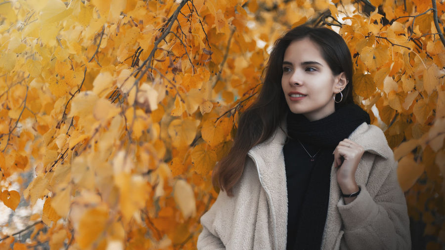 Portrait of young woman standing by maple leaves during autumn