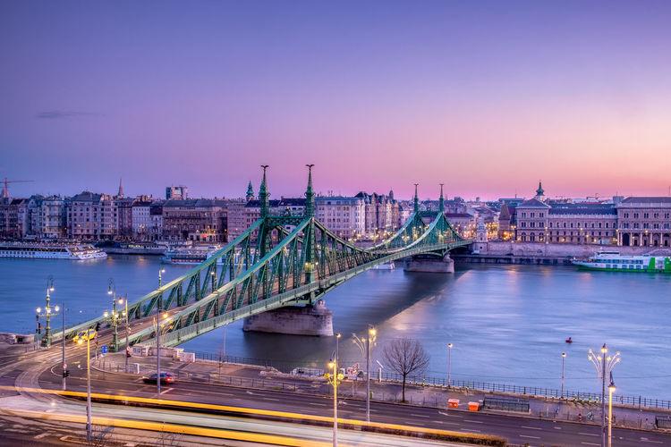Illuminated Liberty Bridge Over Danube River Against Sky At Night