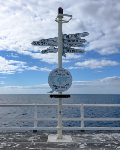 Information sign by sea against sky