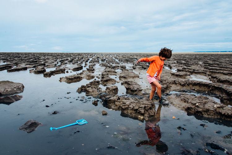 Side view of boy walking on rocky beach against sky