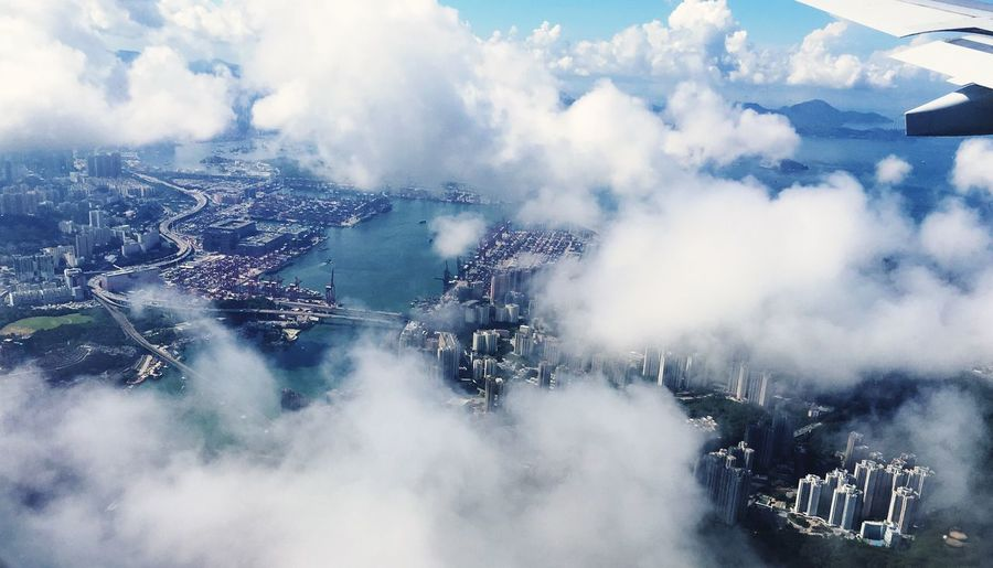 Aerial view of city against cloudy sky