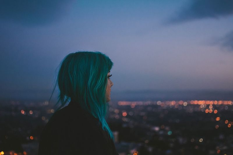 Side view of thoughtful woman standing against illuminated city at dusk
