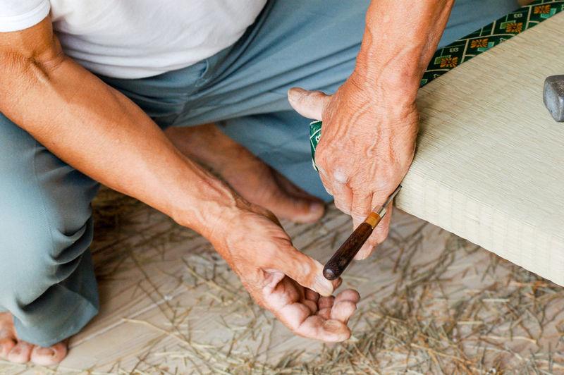 High Angle View Of Man Repairing Tatami Mat At Home