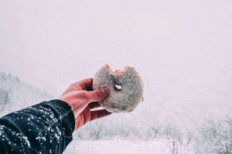 Close-Up Of Hand Holding Donut Against Sky During Winter