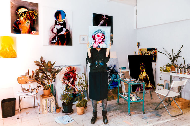 Woman holding painting against face while standing at art studio