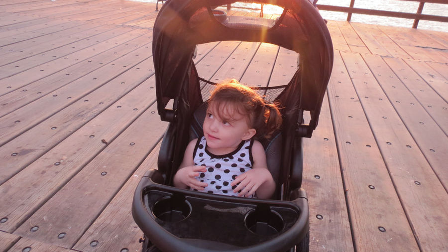 Girl Sitting In Baby Carriage On Deck