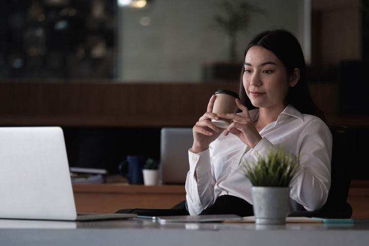 Mid adult woman using mobile phone at table