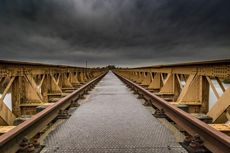 Railway bridge over water against sky