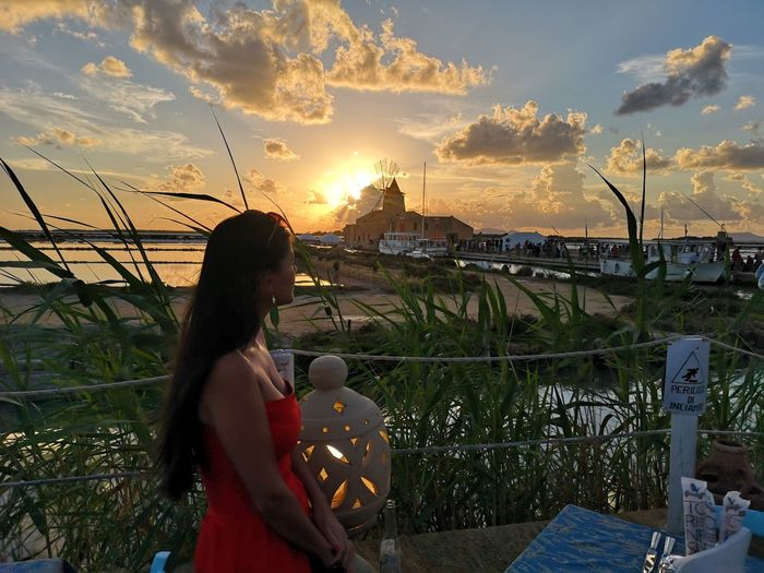 Side view of woman standing against sky during sunset