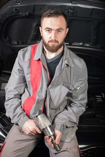 Portrait of male mechanic holding tool while sitting on chair