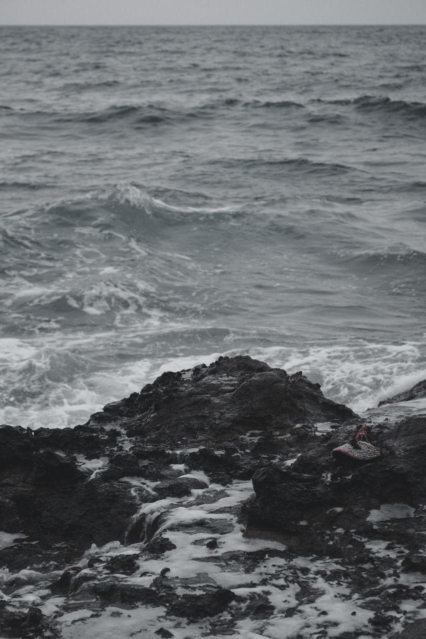 SCENIC VIEW OF SEA AGAINST ROCKY SHORE