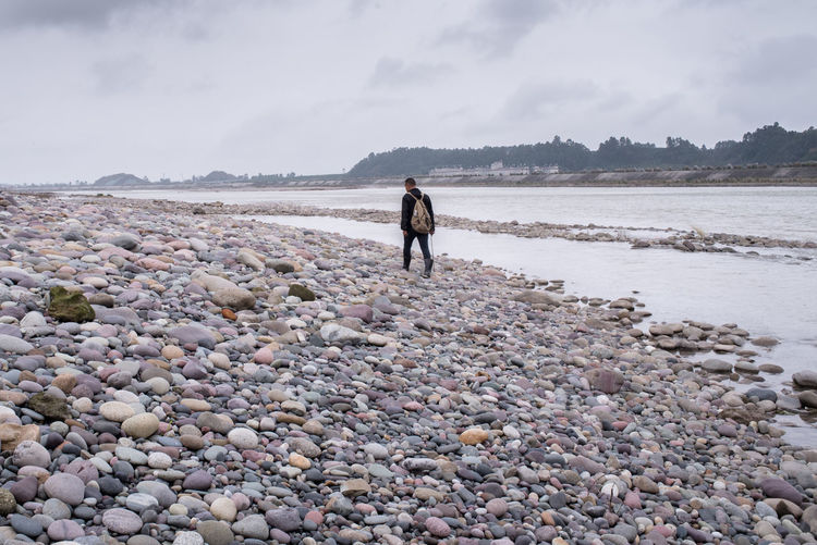 Man walking along a river, searching special pebbles for collection. Artist Business Man Beach Collection Collector Hobby Leisure Activity Lifestyles One Person Outdoors Pebble Pebble Beach People Real People River Riverbank Searching Shingle Beach Shore Sky Walking Young Adult