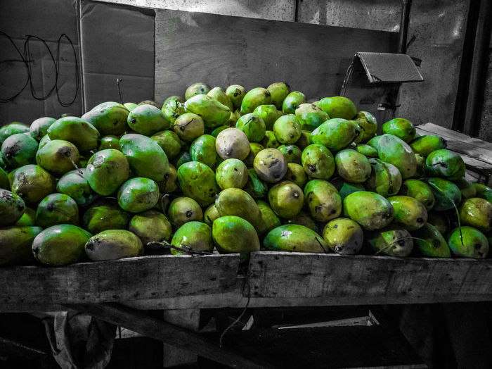 Green fruits for sale at market stall