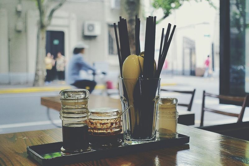 Sauce and drinking straws in glass on restaurant table