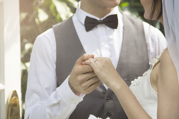 Midsection of bride and groom holding hands at wedding
