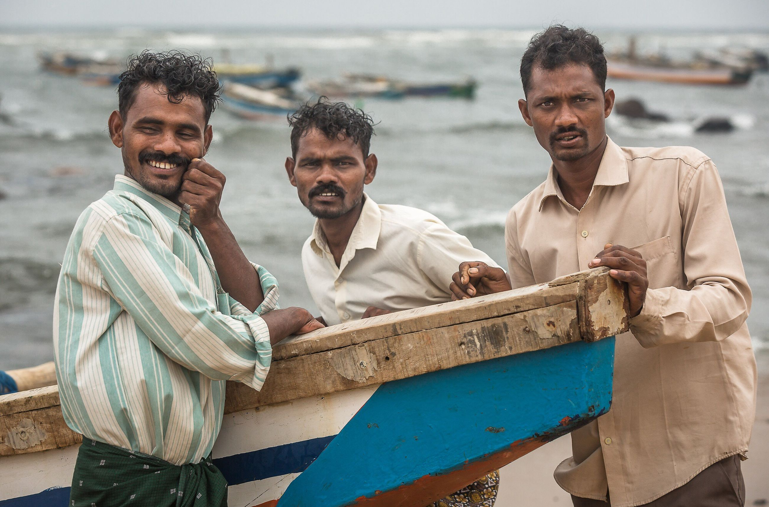 lifestyles, young men, person, leisure activity, casual clothing, togetherness, smiling, water, sitting, mid adult men, happiness, bonding, front view, nautical vessel, boys, young adult, men