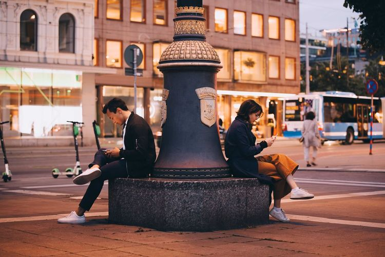 Man sitting by statue against buildings in city