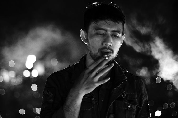 Portrait of man smoking cigarette against sky at night