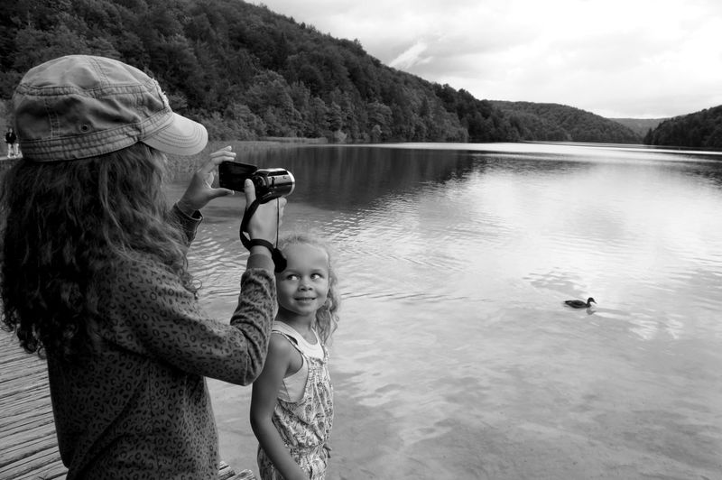 Girl holding camera with sister by lake at plitvice lakes national park