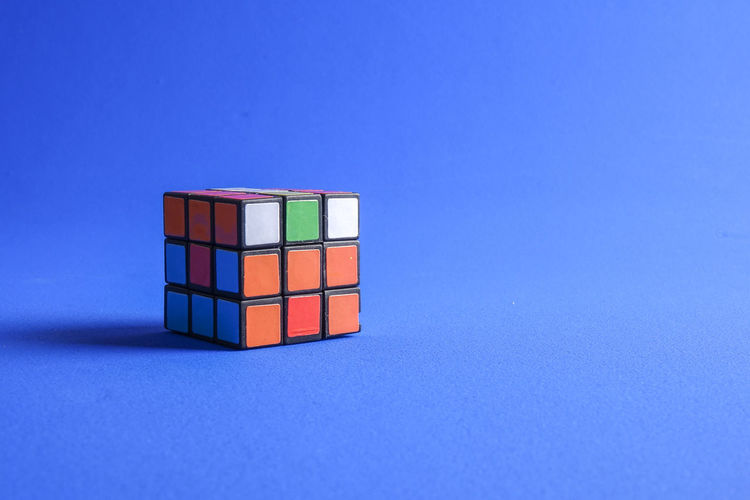 RUBIK'S CUBE , CREATIVITY TOY Creativity Rubik Cube Blue Blue Background Close-up Colored Background Copy Space Cube Shape Geometric Shape Indoors  Intelligence Leisure Games Multi Colored No People Orange Color Red Relaxation Rubik Shape Stack Still Life Studio Shot Table Toy