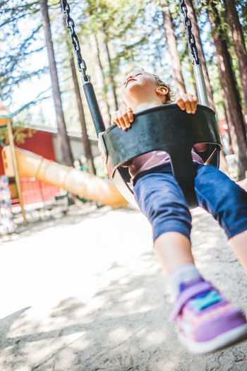 Leisure Activity Real People One Person Casual Clothing Full Length Day Childhood Child Enjoyment Men Nature Selective Focus Lifestyles Low Angle View Outdoors Fun Balance Innocence Playing Girl Park Swing