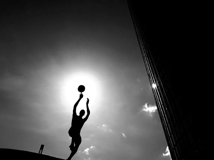 Low angle view of silhouette man playing with ball against sky