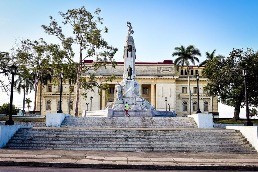 Palm Tree Tree Steps Statue Architecture Sculpture Built Structure Human Representation Building Exterior Religion Sky Spirituality Day Travel Destinations Low Angle View Outdoors No People Clear Sky Santa Clara Cuba Cuba The Street Photographer - 2017 EyeEm Awards