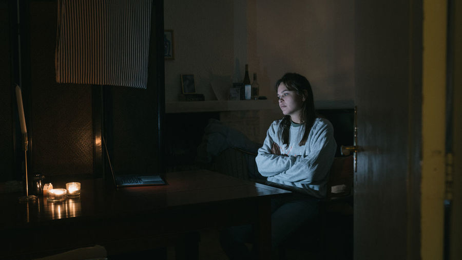 Young woman watching video over laptop on table at home