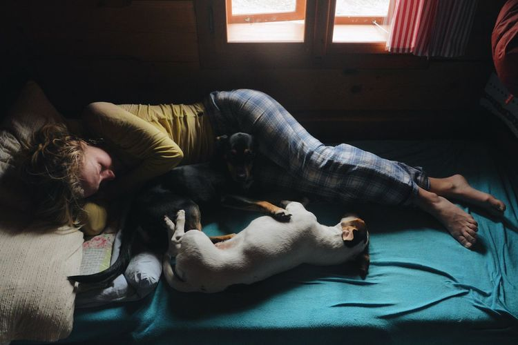 Woman with dogs relaxing on bed