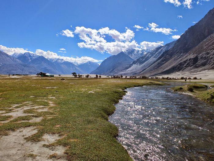 River stream on landscape against sky in nubra valley