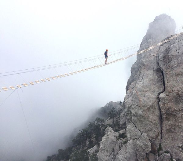 Woman on rope bridge during foggy weather