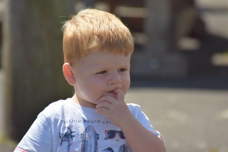 Close-Up Of Cute Boy Biting Nail