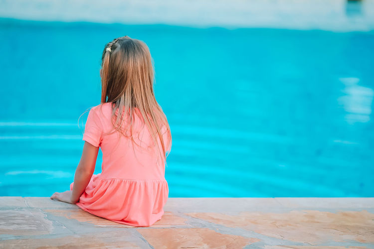 Rear view of view of girl sitting by swimming pool