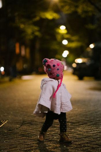 Full length of girl standing on street at night
