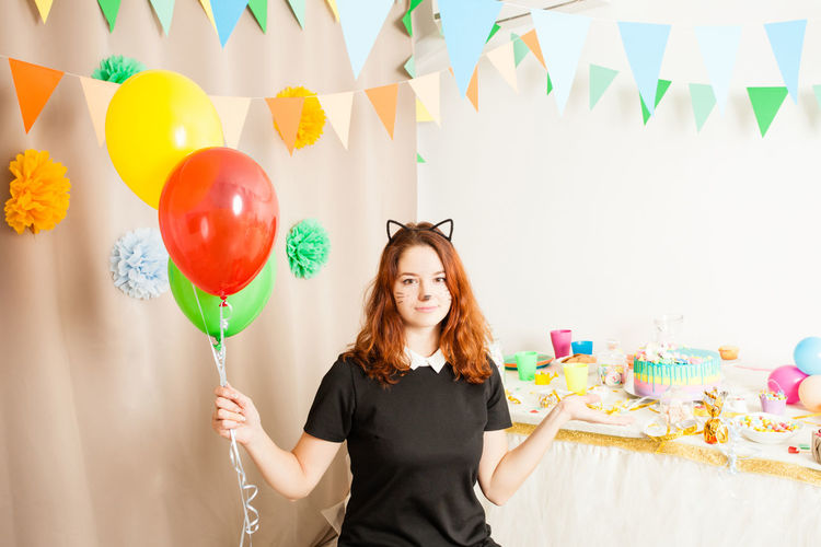 Portrait of smiling woman standing with balloons