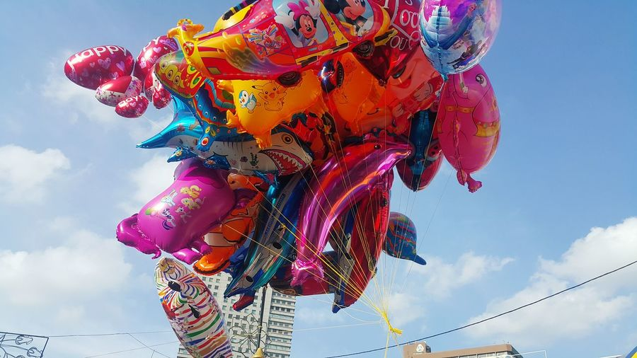 Low angle view of colorful inflatable balloons against sky